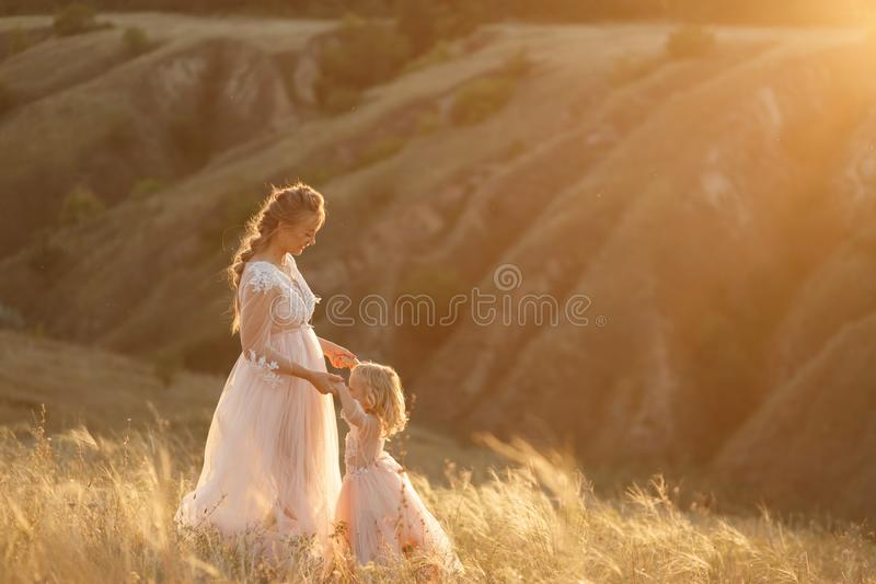 Mom with daughter in pink fabulous dresses in nature, holding hands. Sunset sun rays royalty free stock photo