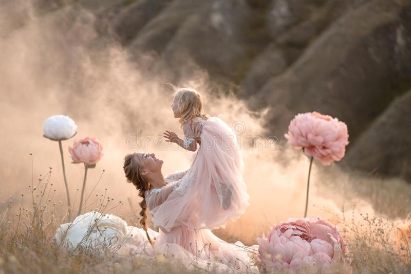 Mom and daughter in pink fairy-tale dresses play in a field surrounded by Big pink decorative flowers stock photo