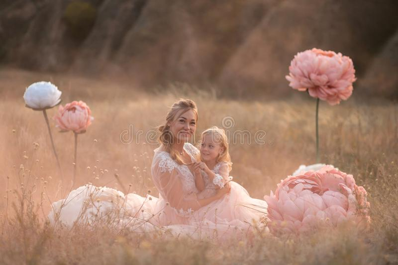 Mom and daughter in pink fairy-tale dresses are sitting in a field surrounded by Big pink decorative flowers stock photo