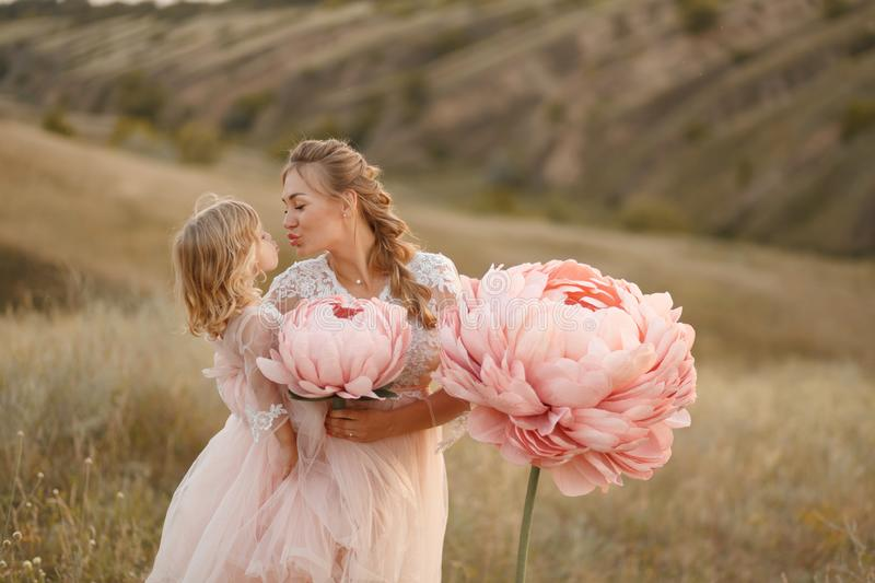 Mom with daughter in pink fairy-tale dresses walk in nature. The childhood of the little princess. Large pink decorative flowers stock photos