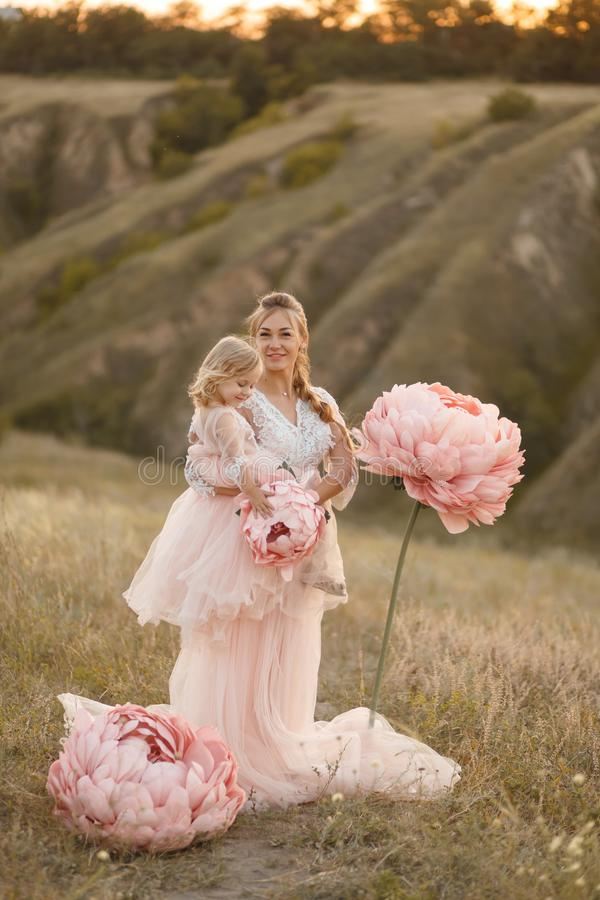 Mom with daughter in pink fairy-tale dresses walk in nature. The childhood of the little princess. Large pink decorative flowers royalty free stock photos