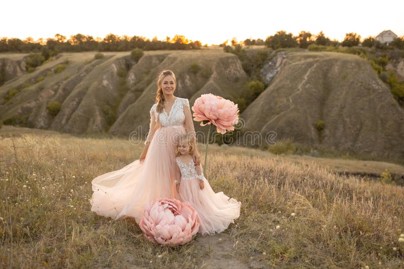 Mom with daughter in pink fairy-tale dresses walk in nature. The childhood of the little princess. Large pink decorative flowers stock image