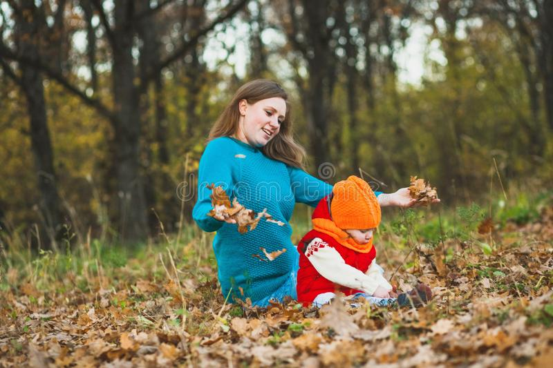 Mom and daughter play in the autumn foliage stock photo