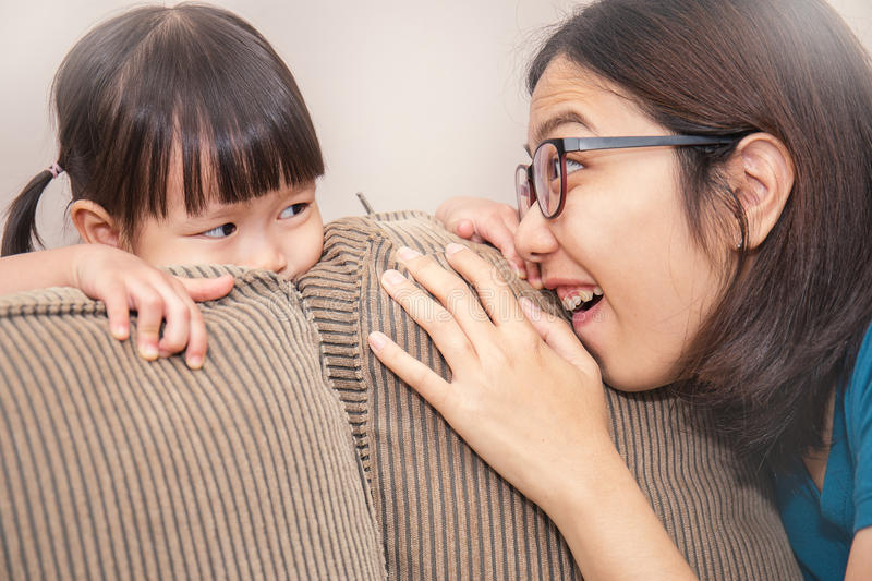 Mom and daughter play hide and seek stock photos
