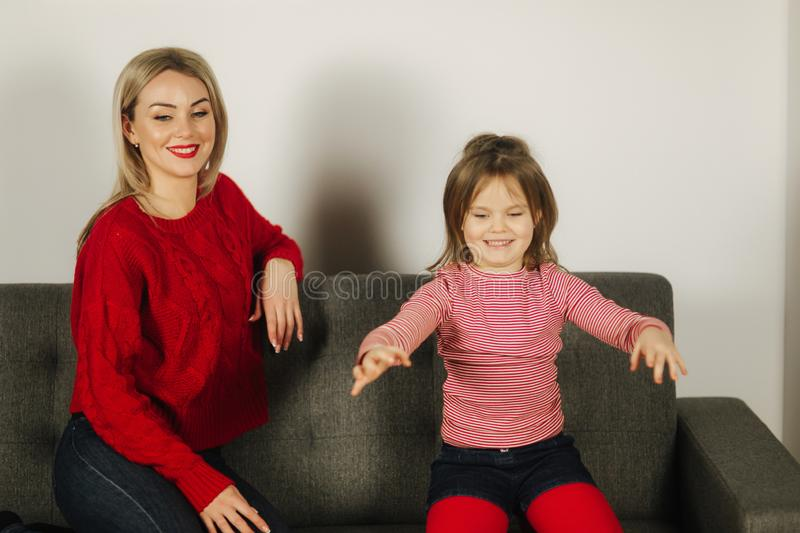 Mom and daughter play at home. Little girl tickle her mother. Happy family spend time together. Blond hair woman stock photos