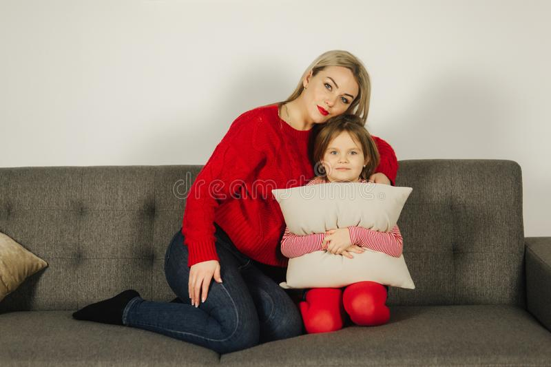 Mom and daughter play at home. Little girl tickle her mother. Happy family spend time together. Blond hair woman stock photography