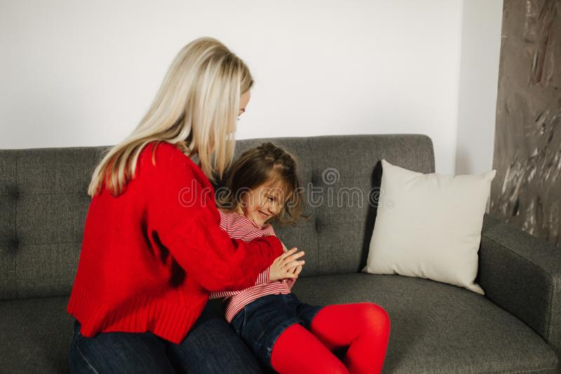 Mom and daughter play at home. Little girl tickle her mother. Happy family spend time together. Blond hair woman royalty free stock image