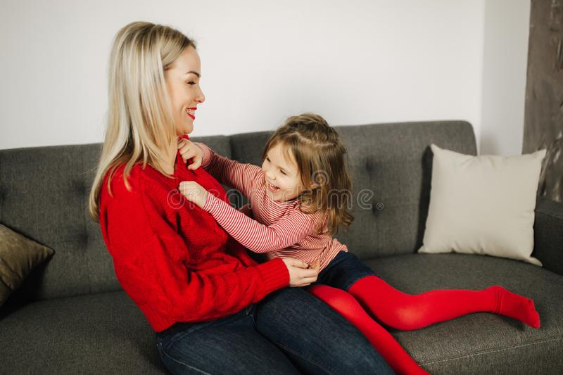 Mom and daughter play at home. Little girl tickle her mother. Happy family spend time together. Blond hair woman royalty free stock photography