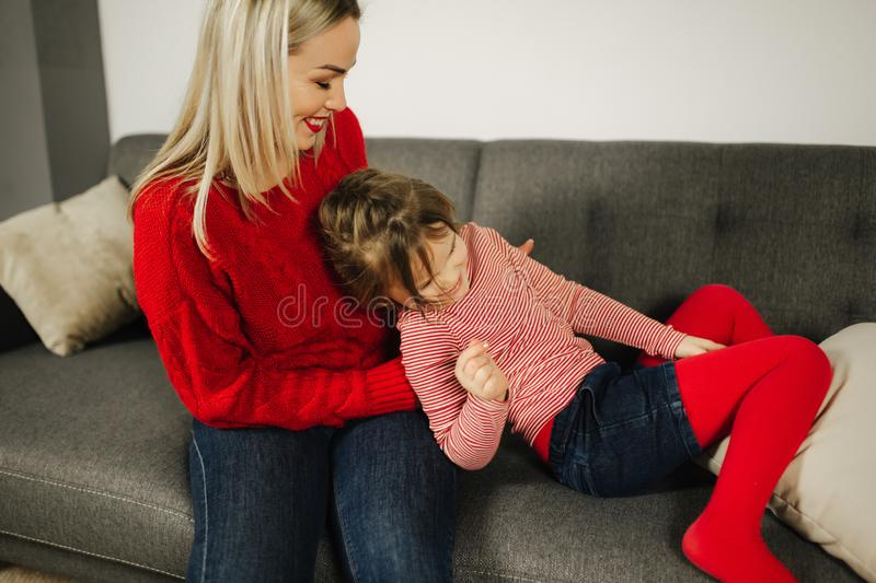 Mom and daughter play at home. Little girl tickle her mother. Happy family spend time together. Blond hair woman stock images