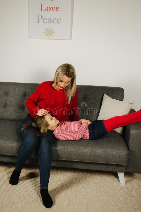 Mom and daughter play at home. Little girl tickle her mother. Happy family spend time together. Blond hair woman stock image
