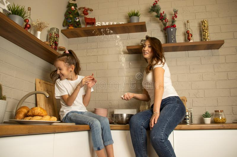 Mom and daughter are playing in the kitchen, messing with flour stock photo