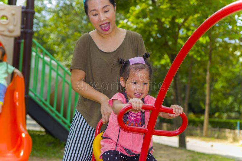 Mom and daughter  playing on play ground play slider seesaw,  Funny Asian family in a park. High resolution image gallery royalty free stock images