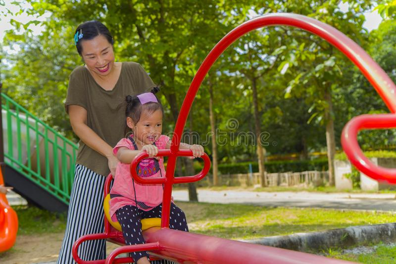 Mom and daughter  playing on play ground play slider seesaw,  Funny Asian family in a park. High resolution image gallery royalty free stock image