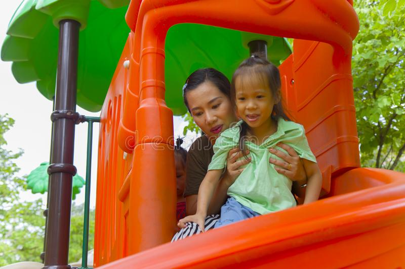 Mom and daughter  playing on play ground play slider seesaw,  Funny Asian family in a park royalty free stock image
