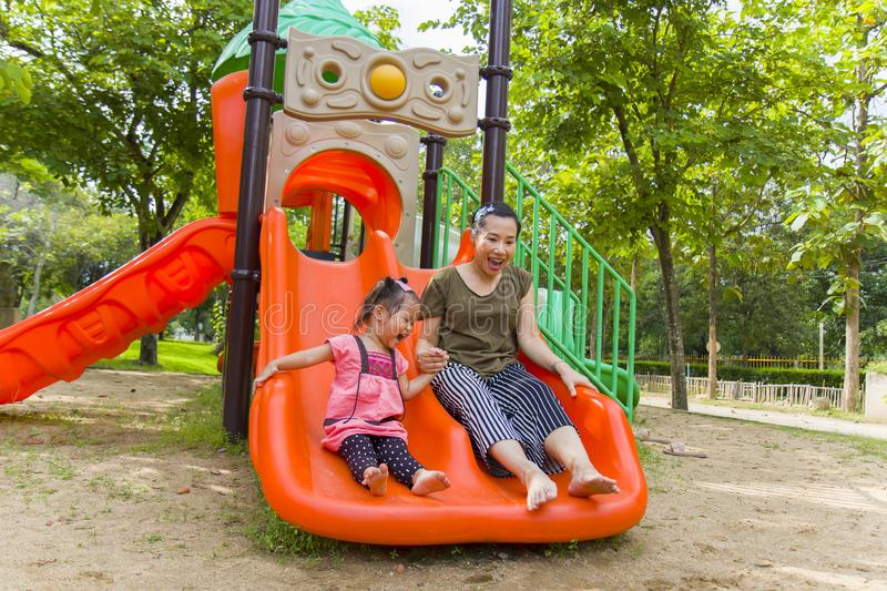 Mom and daughter  playing on play ground play slider seesaw,  Funny Asian family in a park. High resolution image gallery royalty free stock photo