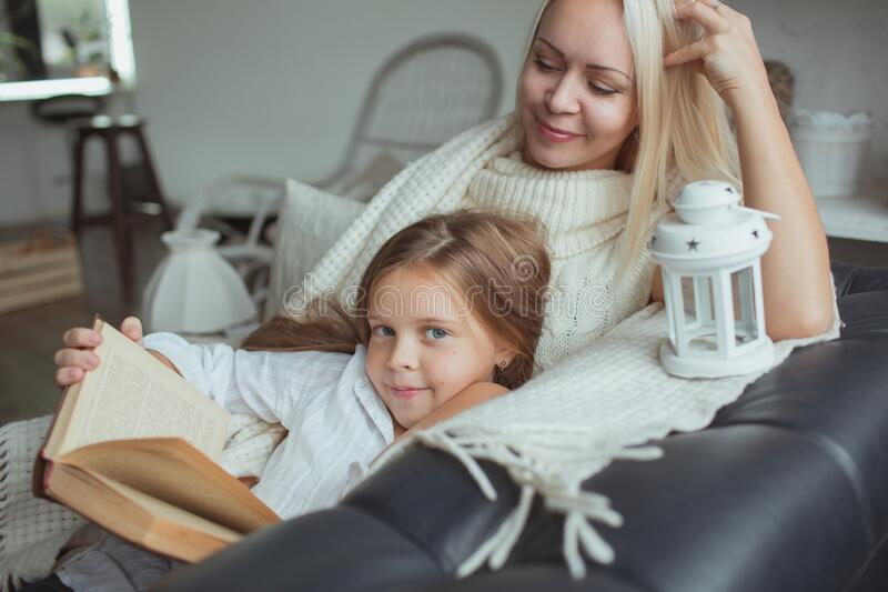 Mom and daughter read a book at home. stock photos