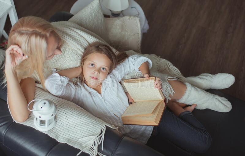 Mom and daughter read a book at home. royalty free stock photos