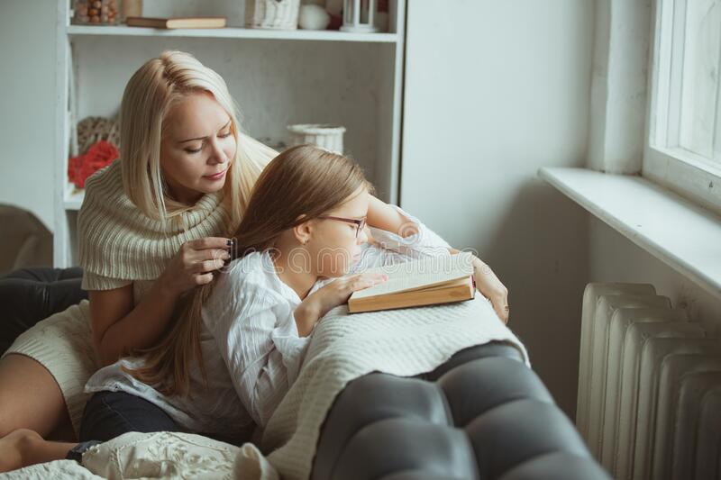 Mom and daughter read a book at home. royalty free stock images