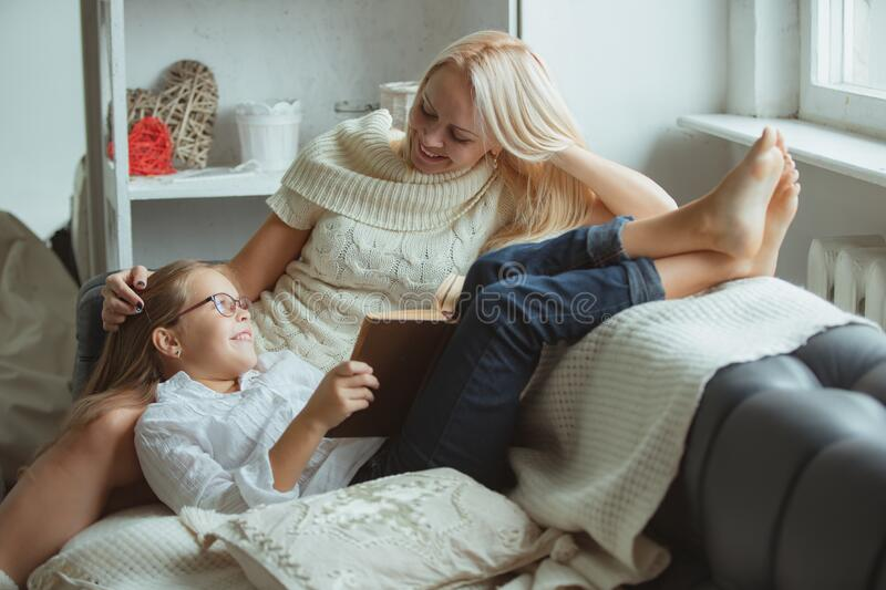 Mom and daughter read a book at home. royalty free stock image