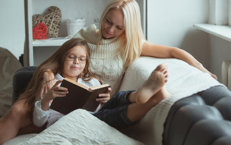 Mom and daughter read a book at home. stock photography
