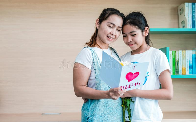Mom and daughter reading a greeting card together royalty free stock photo