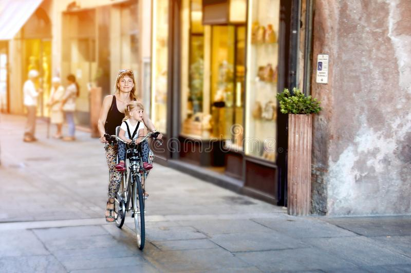 Mom with daughter riding bike in Italy. Child sitting in safety seat. Old narrow italian town. Sport healthy family royalty free stock photography