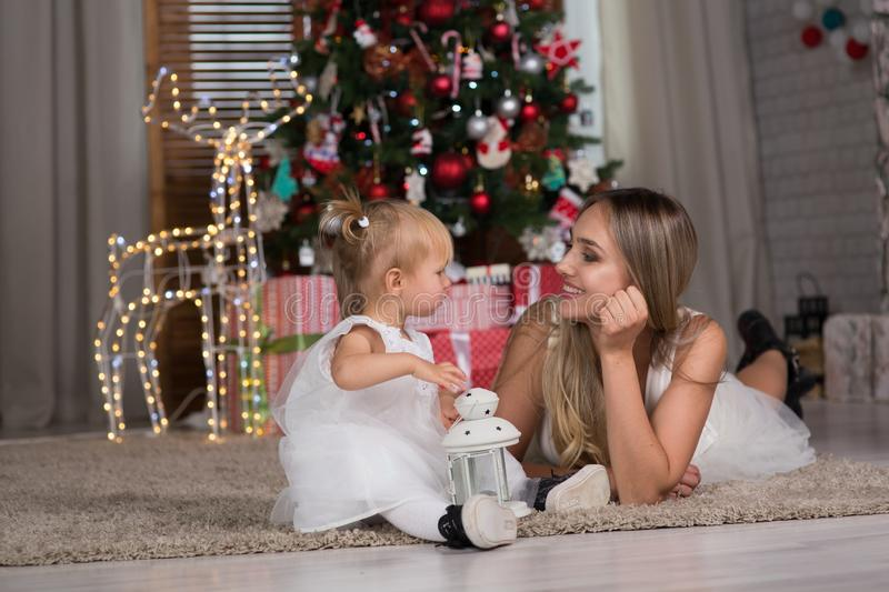 Mom and daughter are sitting around the Christmas tree stock images