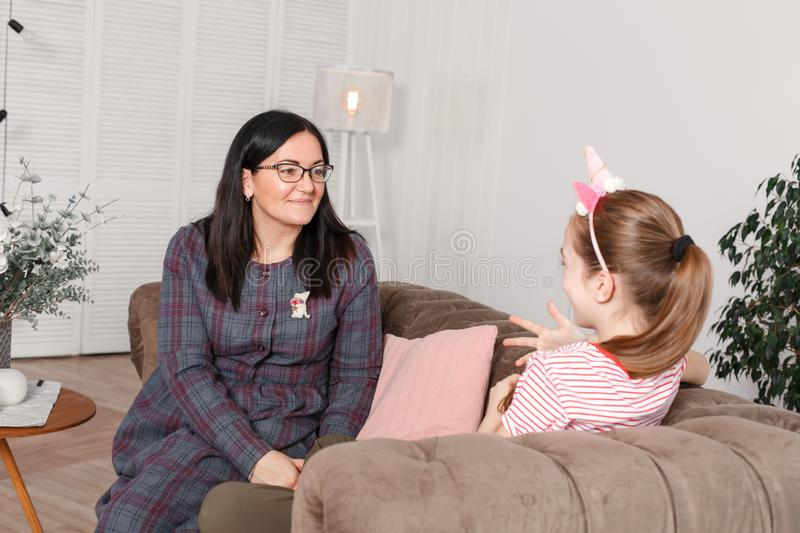 Mom and daughter are sitting on the couch and chatting. Girl teenager with emotions tells her mother a story. Daughter shares her stock photo