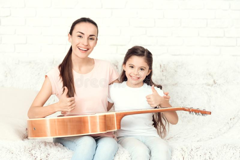 Mom and daughter are sitting on the couch at home. They have a guitar on their laps. Behind them is a white brick wall. A girl and a women are smiling royalty free stock photos