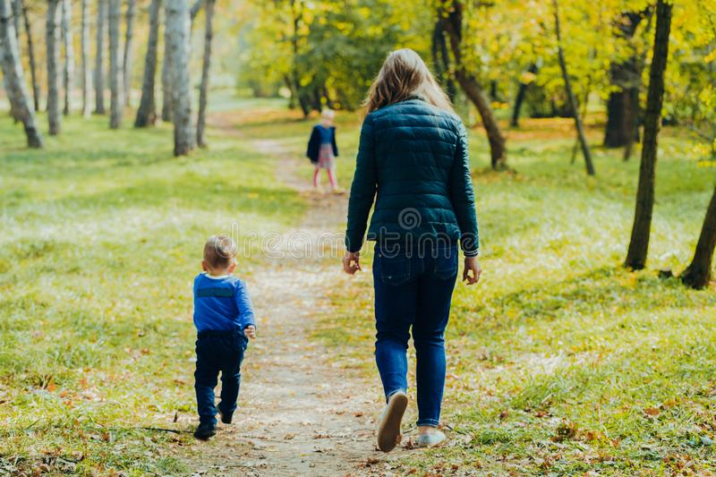 Mom with daughter and son are walking in the autumn park. Family for a walk in the forest stock photo