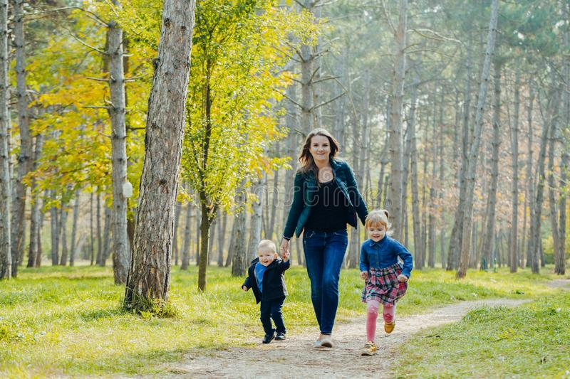 Mom with daughter and son are walking in the autumn park. Family for a walk in the forest royalty free stock photos
