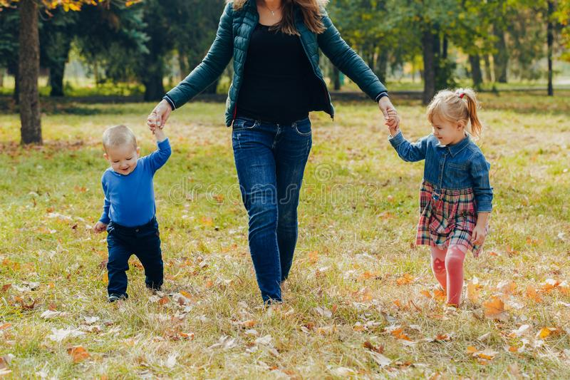 Mom with daughter and son are walking in the autumn park. Family for a walk in the forest stock photography