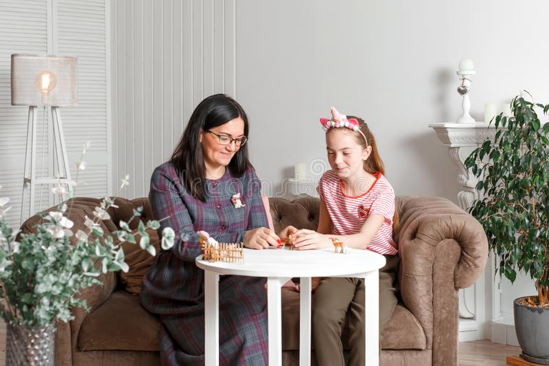 Mom and daughter spend time together, sit on the couch, chatting and playing with toy animals. Leisure mothers and daughters.  royalty free stock images