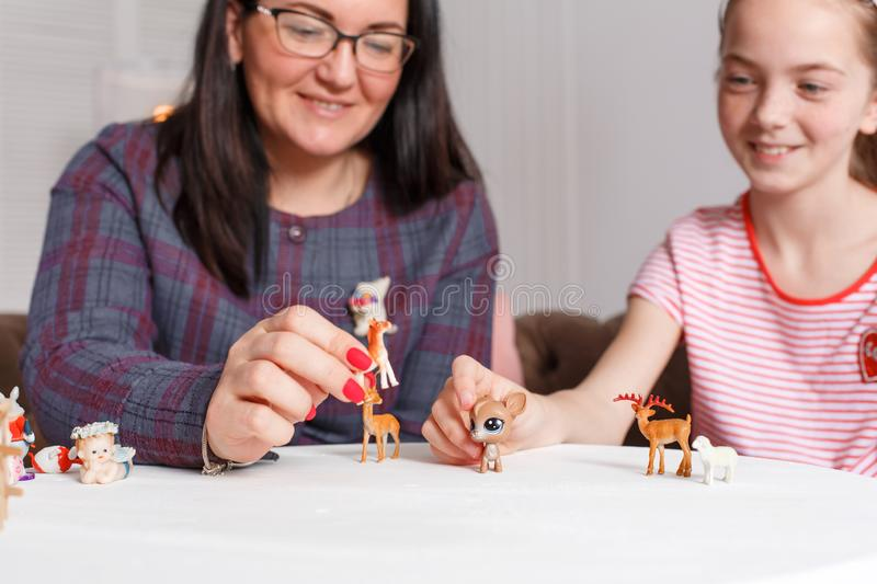 Mom and daughter spend time together, sit on the couch, chatting and playing with toy animals. Leisure mothers and daughters.  royalty free stock image