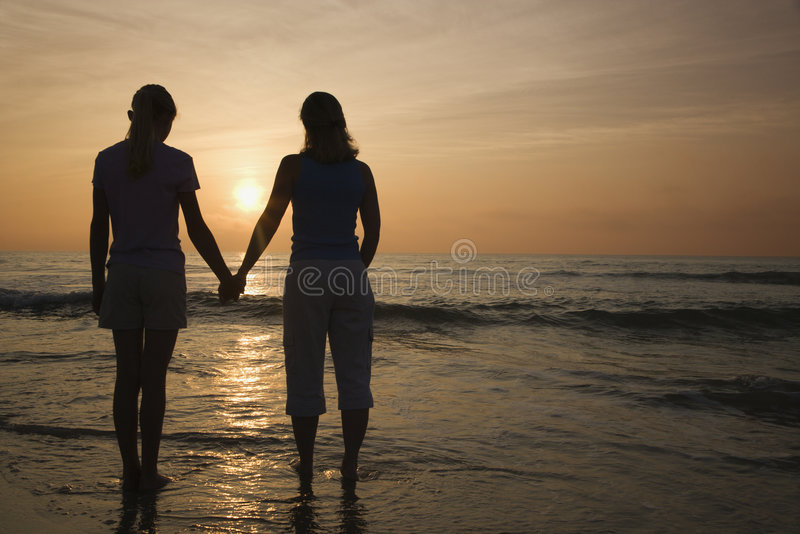 Mom and daughter at sunrise. stock photo