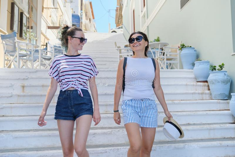Mom and daughter teenager walking talking together. Mom and daughter teenager walking and talking together, summer city resort background white staircase stock photo