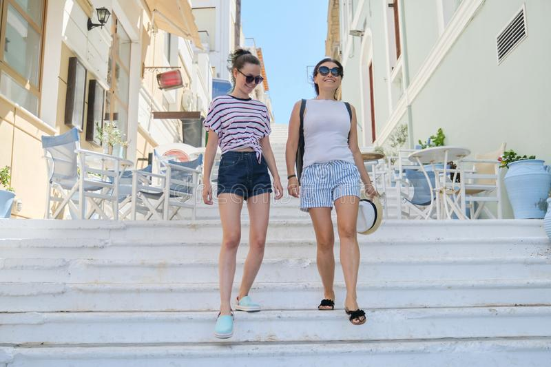 Mom and daughter teenager walking talking together. Mom and daughter teenager walking and talking together, summer city resort background white staircase royalty free stock photo