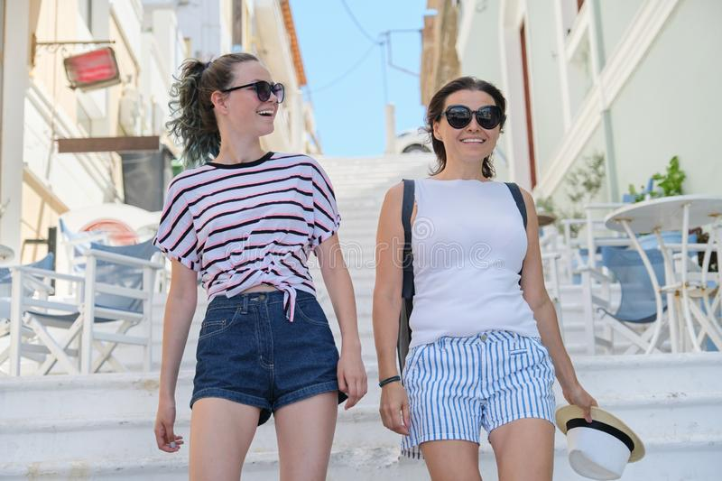 Mom and daughter teenager walking talking together. Mom and daughter teenager walking and talking together, summer city resort background white staircase stock image
