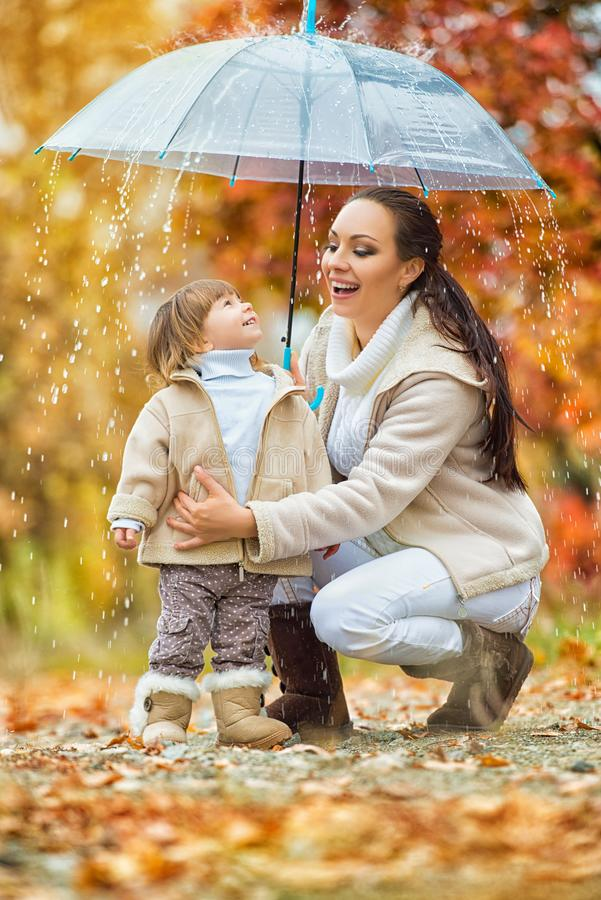 Mom and daughter under the umbrella hide from the rain. stock photography