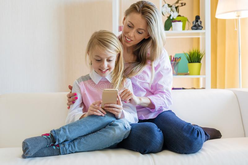 Mom and daughter are using  phone while sitting on the couch stock images