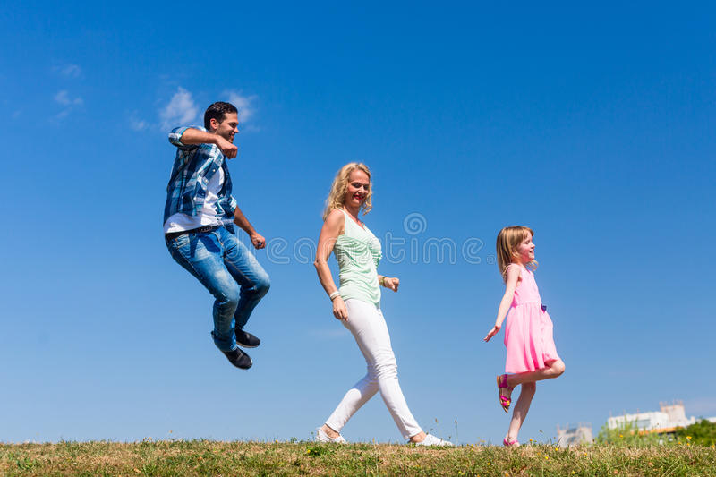 Mom and daughter walk in single file, on is jumping royalty free stock photography