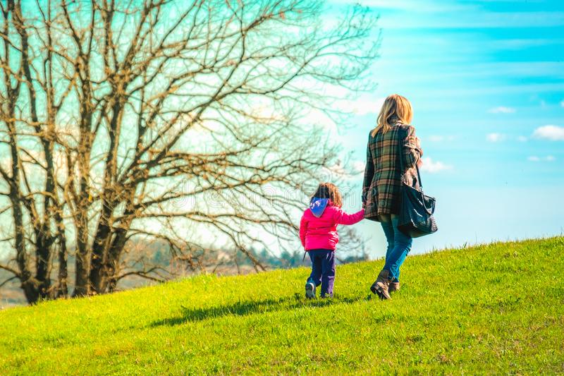 Mom and daughter walk together outside royalty free stock photos