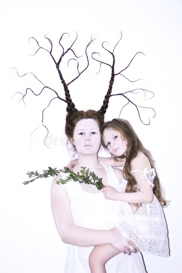 Mom and daughter in white dresses on a white background depict winter and spring, holding flowers and a twig with leaves. Hair bra. Ided in braids. Mom braid is royalty free stock photos