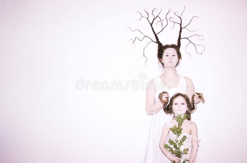 Mom and daughter in white dresses on a white background depict winter and spring, holding flowers and a twig with leaves. Hair braided in braids. Mom braid is royalty free stock photography