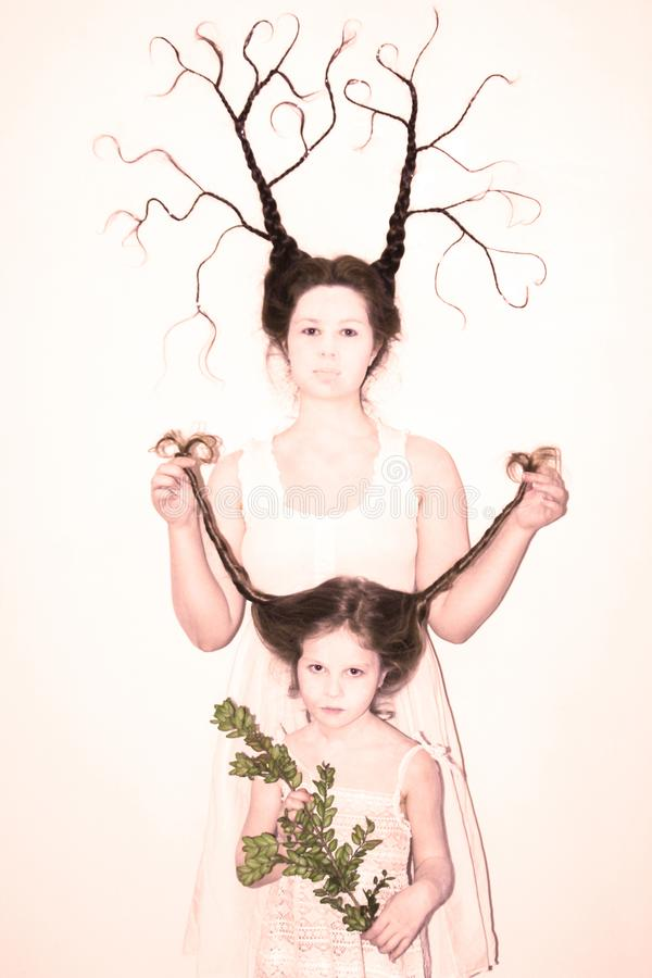 Mom and daughter in white dresses on a white background depict winter and spring, holding flowers and a twig with leaves. Hair braided in braids. Mom braid is royalty free stock photos