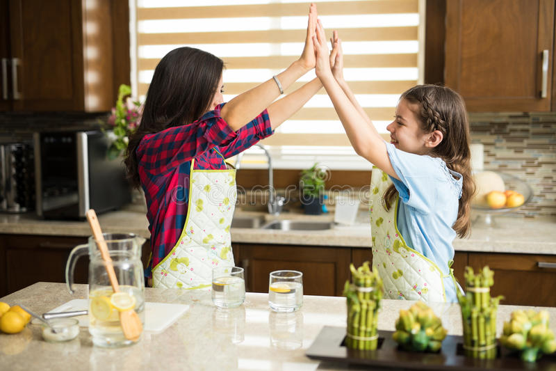 Mom and daughter working together in the kitchen. Profile view of a pretty single mother and her daughter giving high fives while cooking together as a team at stock image