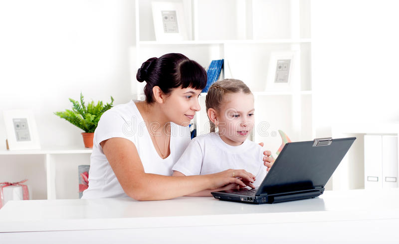 Mom and daughter are working together for a laptop stock photography