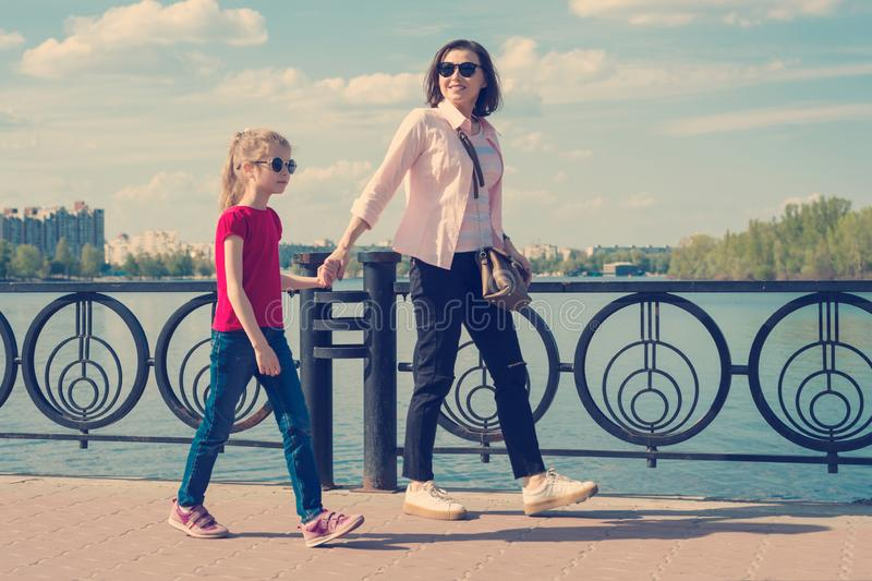 Mom and daughter 7, 8 years go together holding hands, the background of the city embankment the sky in the clouds.  stock images