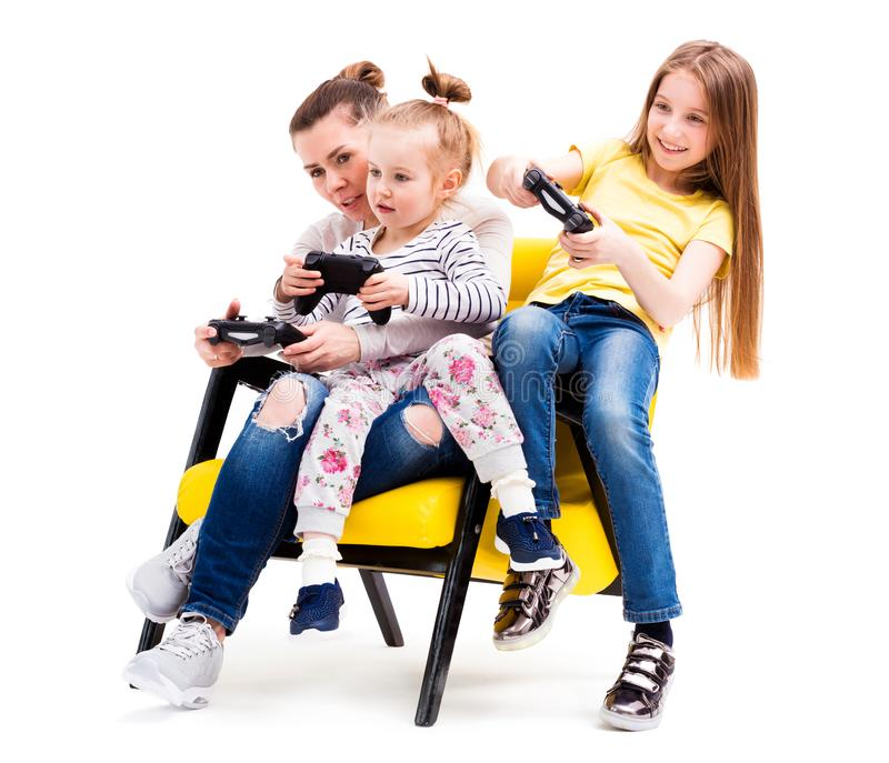 Mom and daughters playing console stock photos