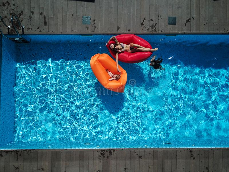 Mom and daughters are resting on the pool. royalty free stock images
